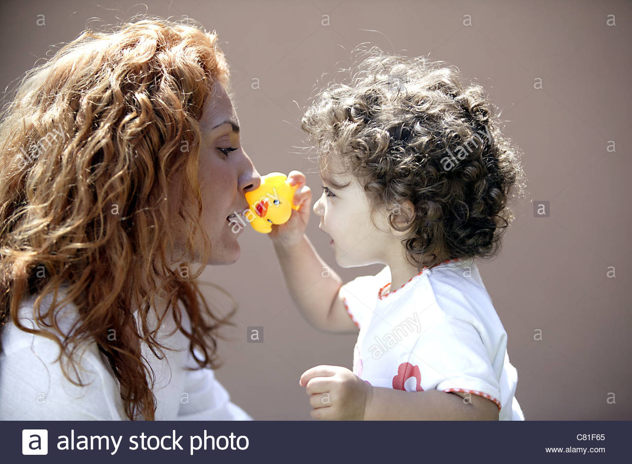 Mother and daughter playing with plastic duck - Stock Image