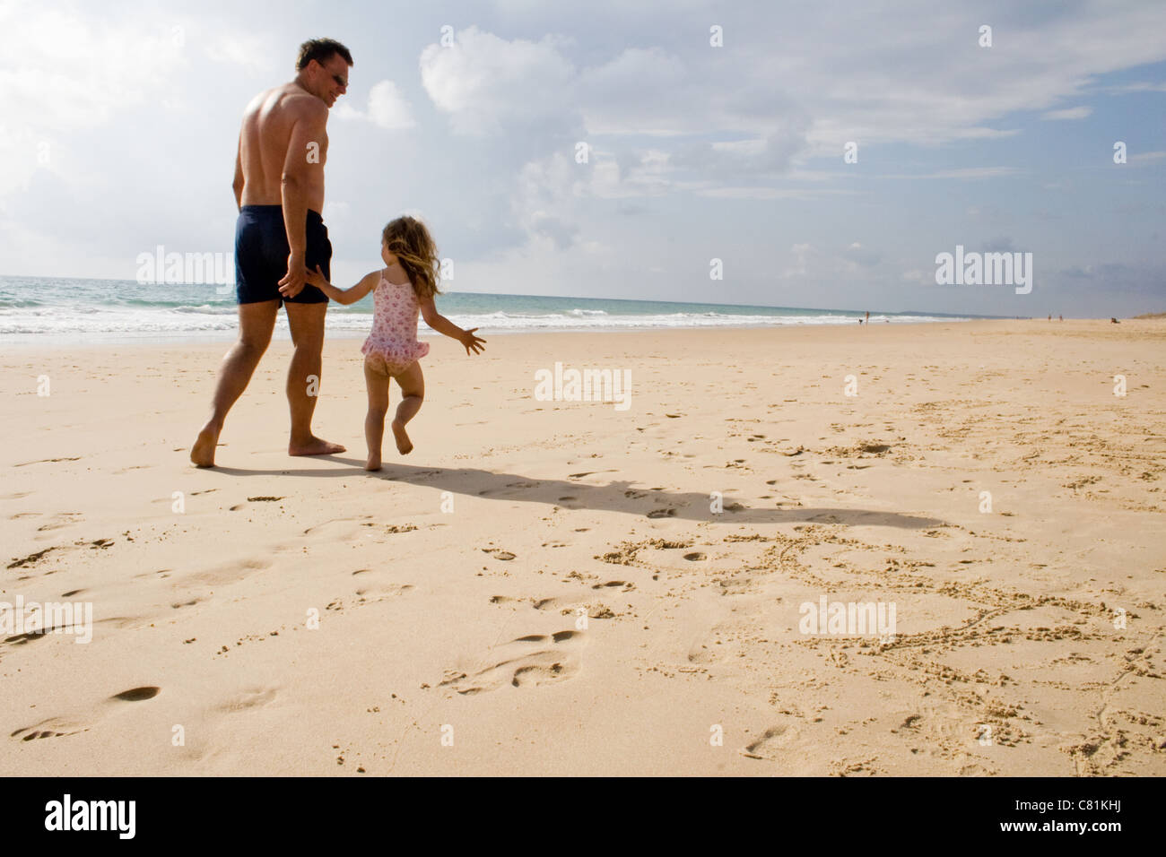 Father Daughter Walking Along The Beach Holding Hands On Holiday