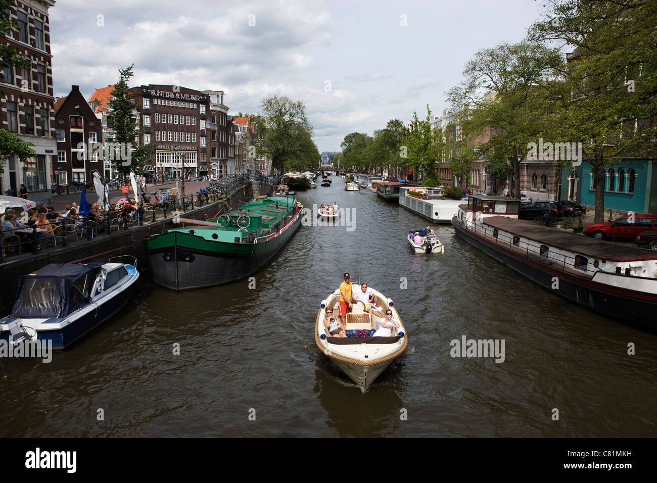 Boats sailing on canal in Amsterdam - Stock Image