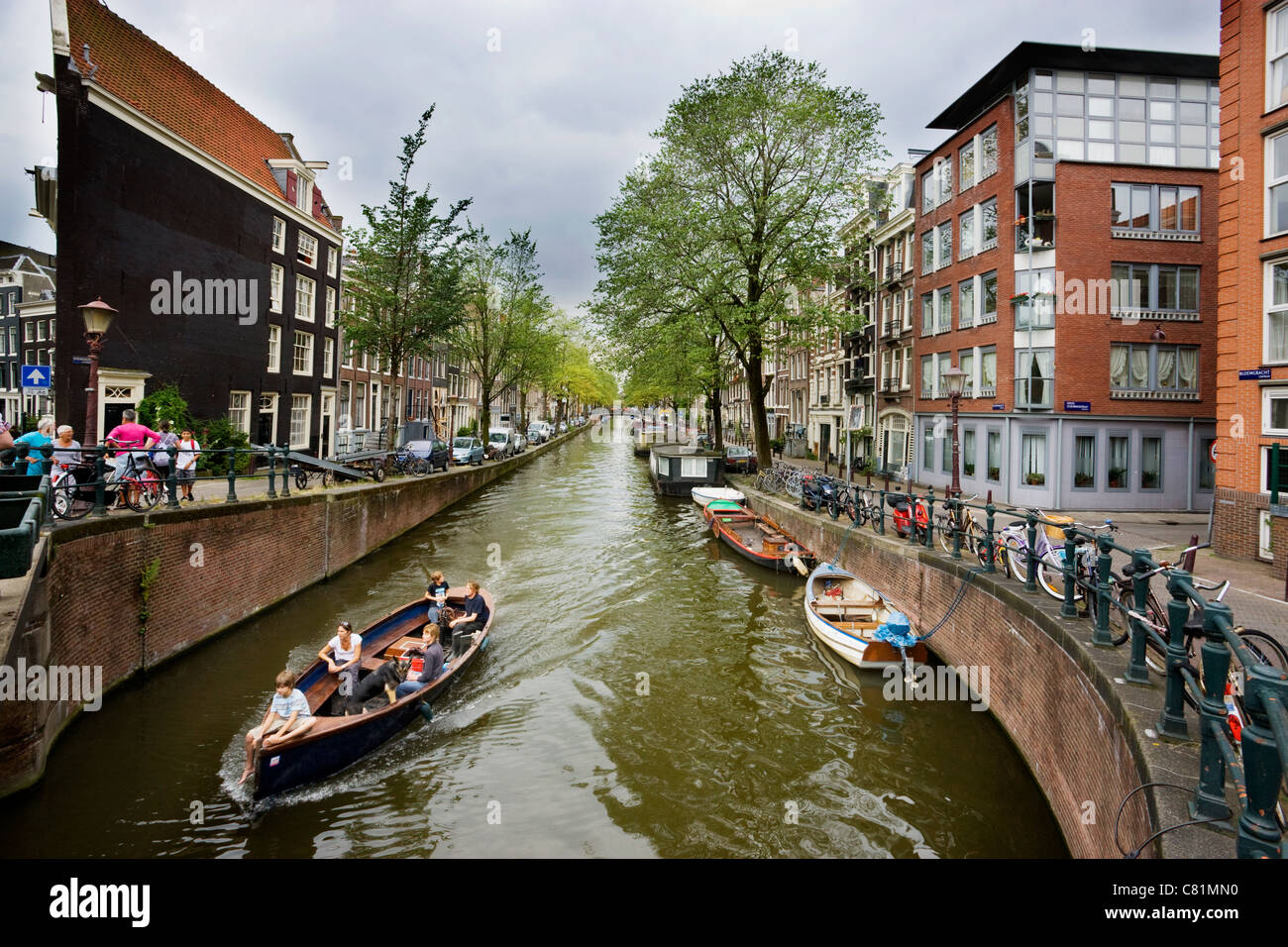 People sailing on canal in Amsterdam - Stock Image