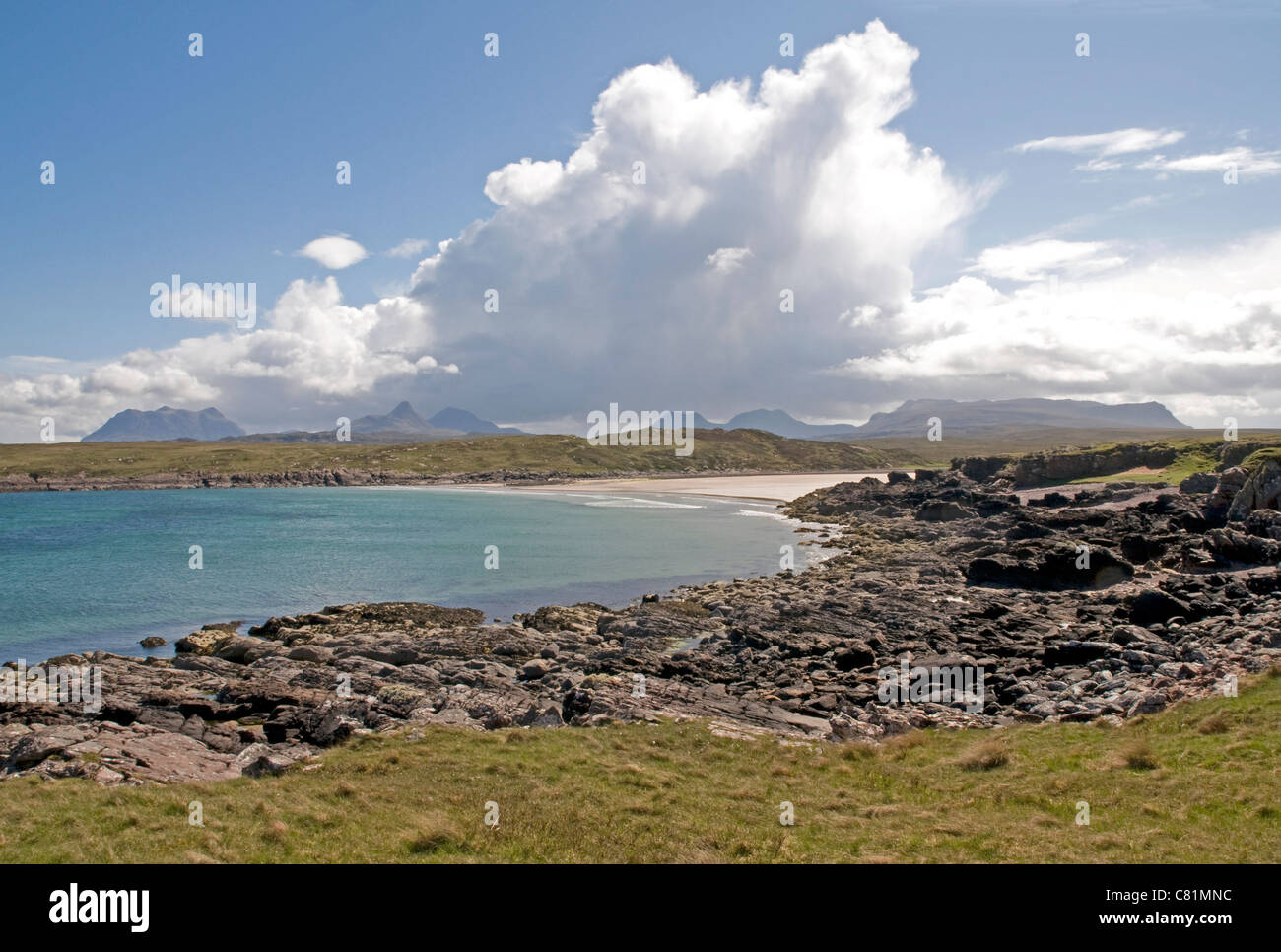 Beach at Achnahaird Bay, Wester Ross, with distant towering cumulonimbus shower clouds over the highlands. - Stock Image