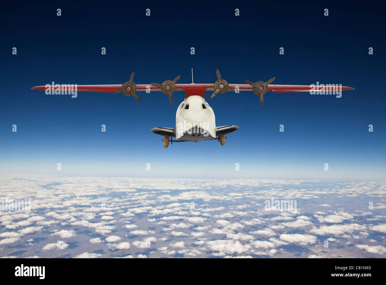 Vintage toy airplane with blue sky aerial background. - Stock Image