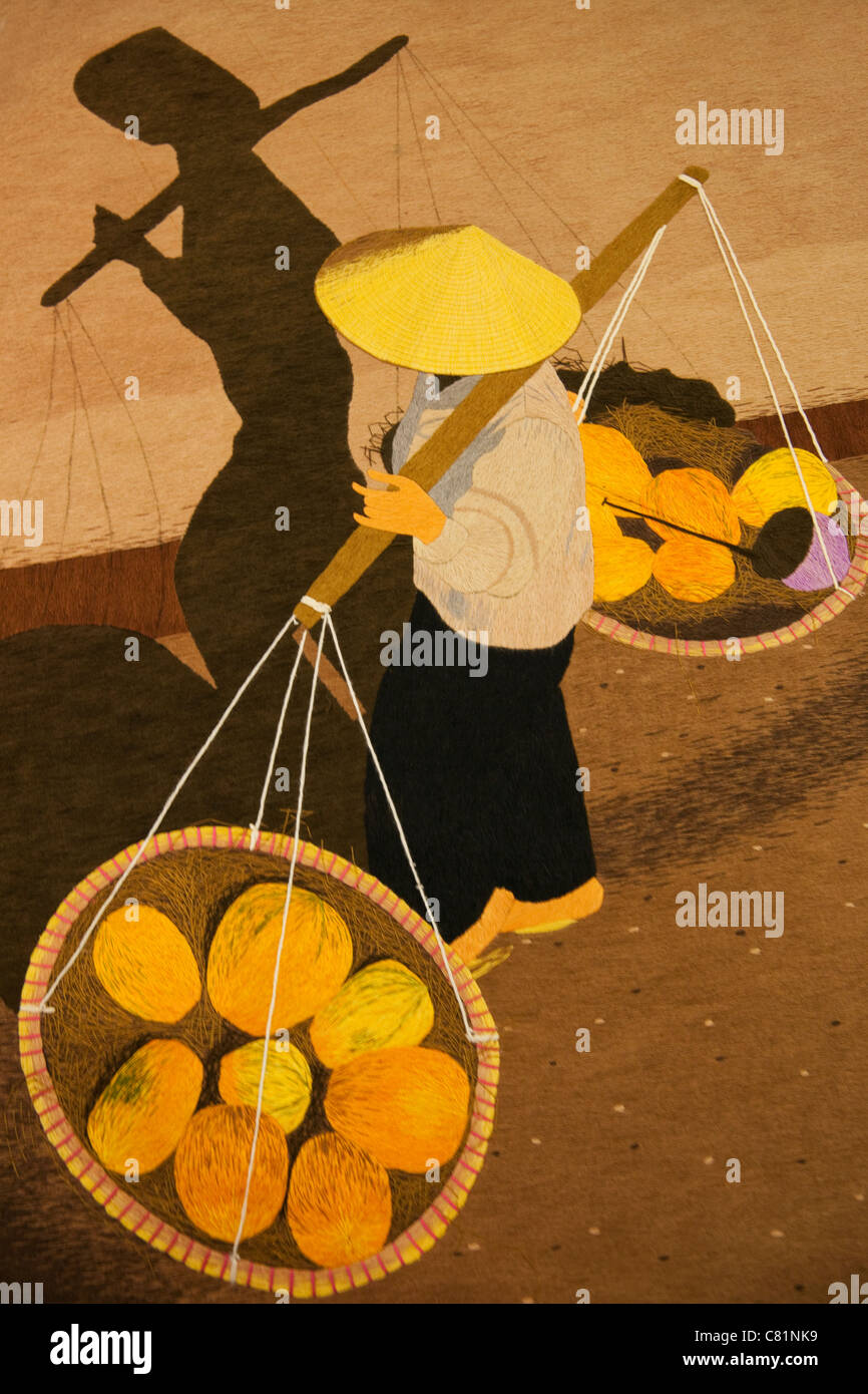 Vietnam, Hanoi, Needlework Picture depicting Woman in Conical Hat Carrying Baskets - Stock Image