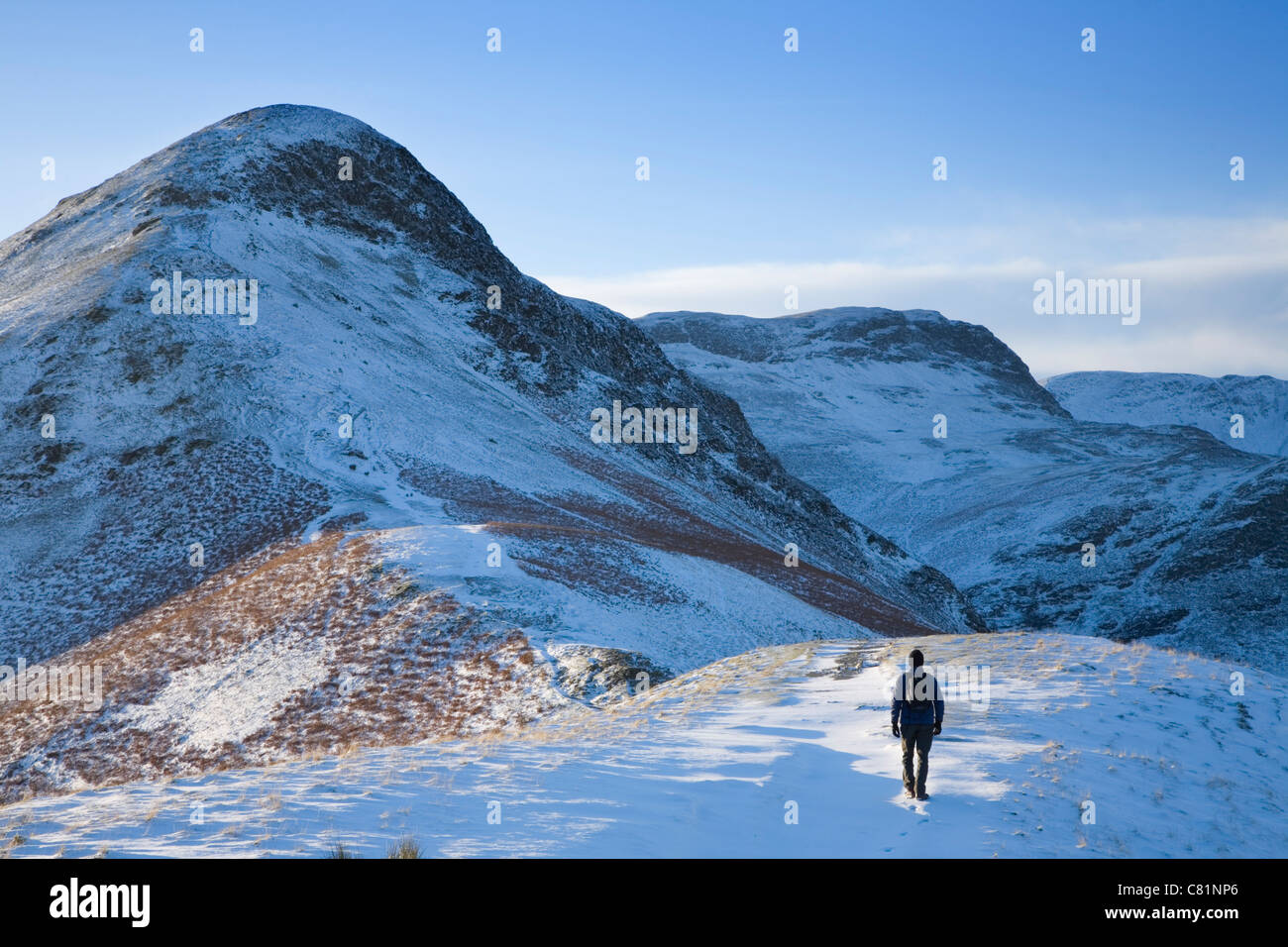 Walker approaching Cat Bells in winter. Lake District National Park. Cumbria, England, UK. - Stock Image