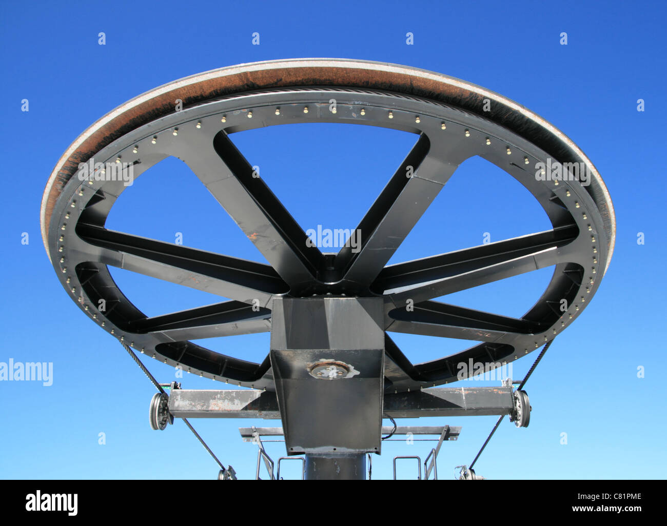 giant pulley wheel from the top of a ski lift with a blue