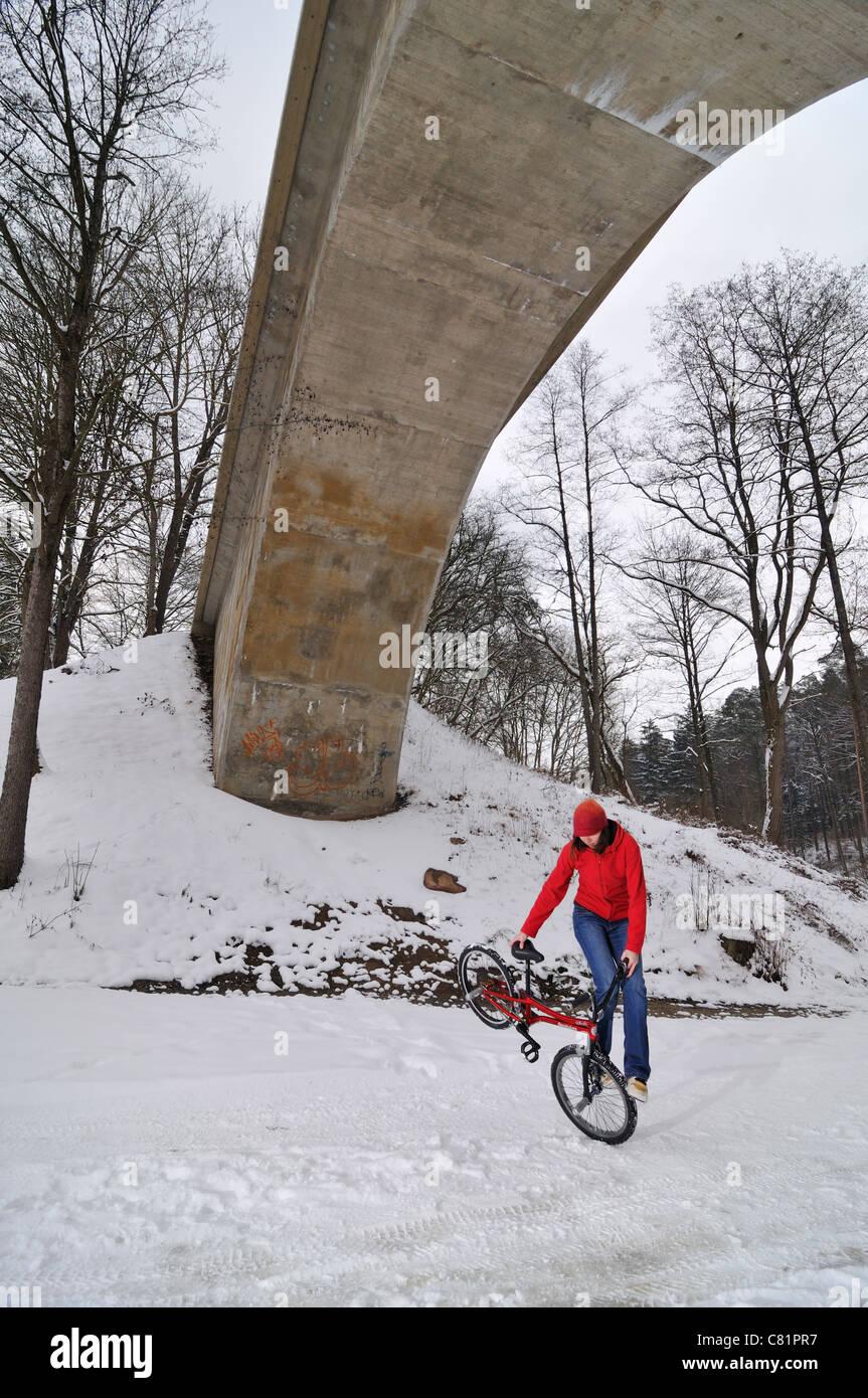 BMX Flatland rider Monika Hinz, riding her bike in the snow, Baden-Wuerttemberg, Germany - Stock Image