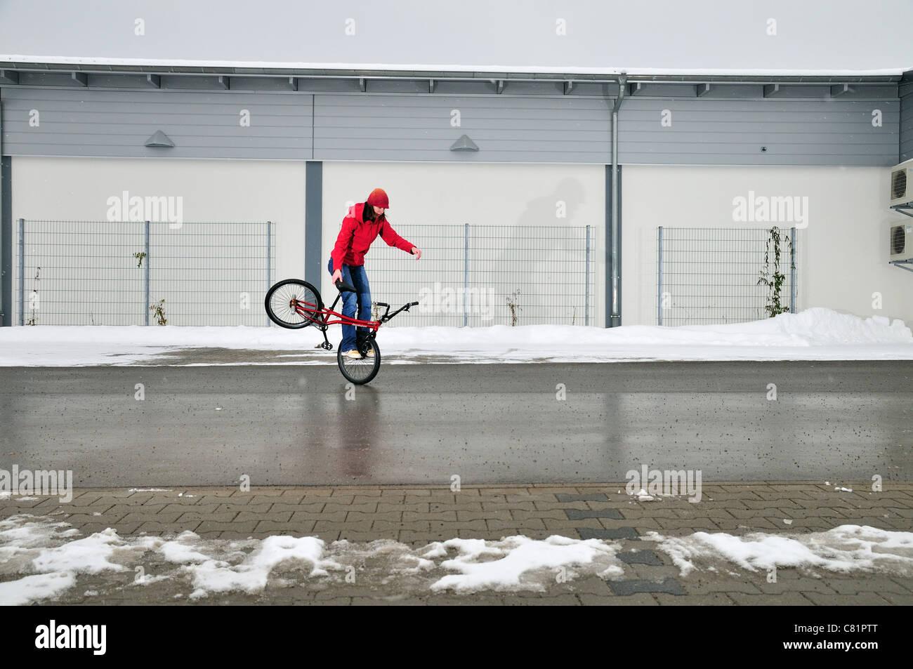 BMX Flatland rider Monika Hinz, riding her bike in winter, Baden-Wuerttemberg, Germany - Stock Image