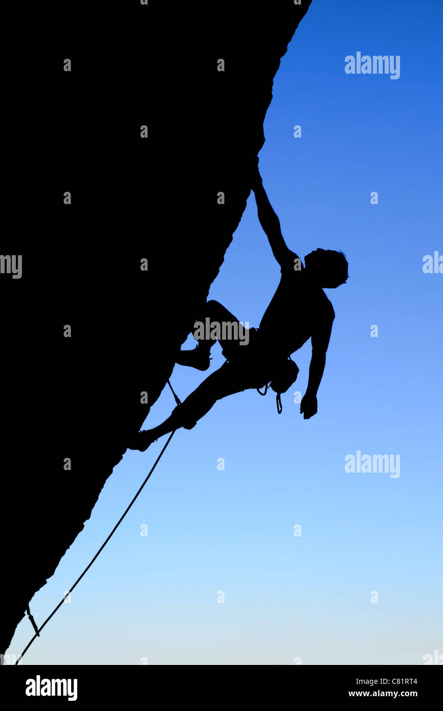 silhouette of rock climber climbing an overhanging cliff with blue sky background - Stock Image