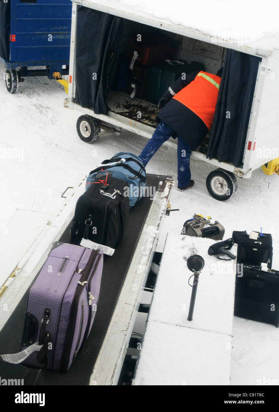 an airline baggage handler loading baggage from a cart onto a conveyor belt on a cold gray snowy day - Stock Image