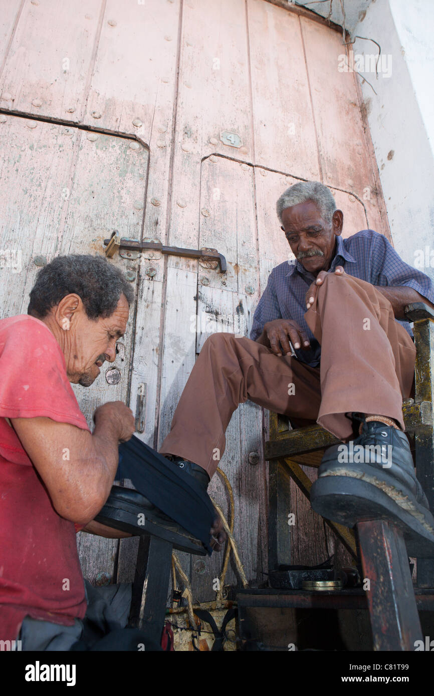 TRINIDAD: MAN HAVING HIS SHOES CLEANED - Stock Image