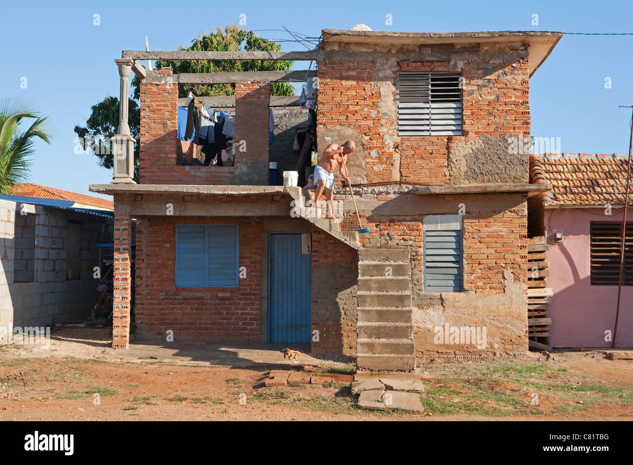 TRINIDAD: MAN SWEEPING STEPS DILAPIDATED HOUSE - Stock Image
