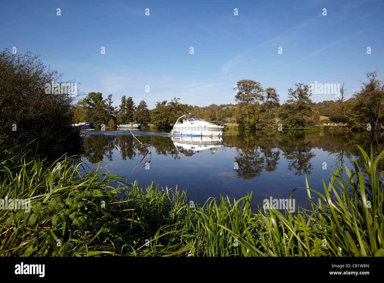 A boat sailing on the River Thames near to Pangbourne, Reading, Berkshire. - Stock Image