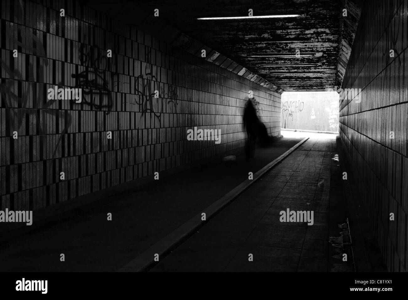 Shadowy figure walking in graffiti covered subway - Stock Image