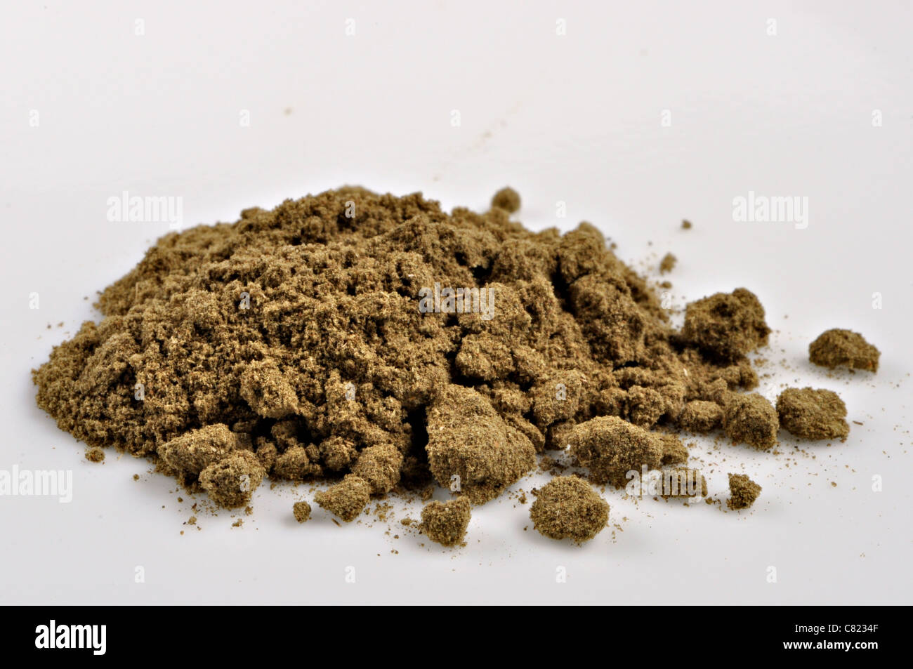 A small pile of ground marjoram sits on a white plate - Stock Image