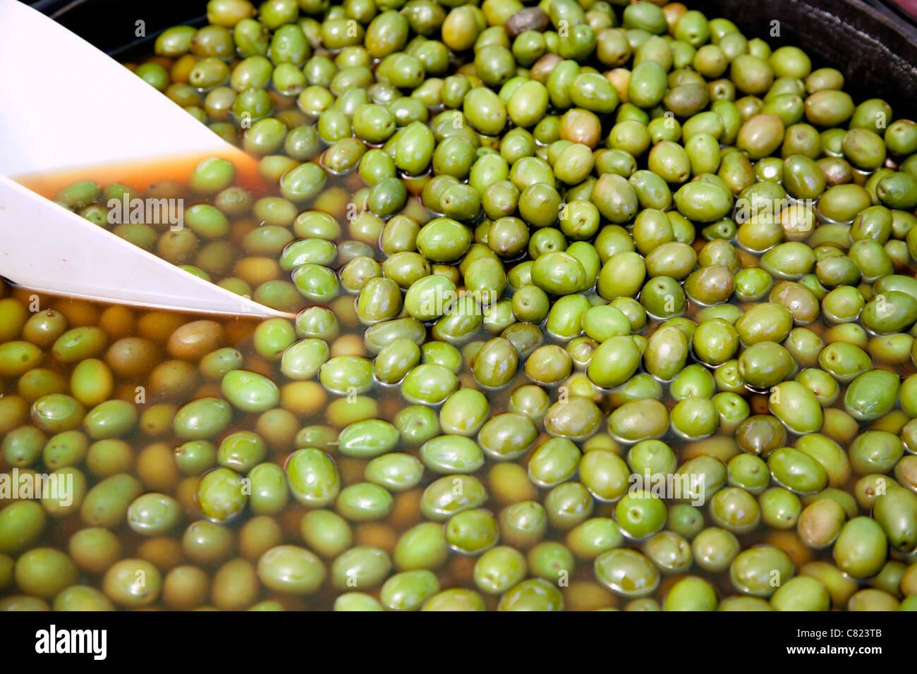brine green olive fruits in market round pot - Stock Image