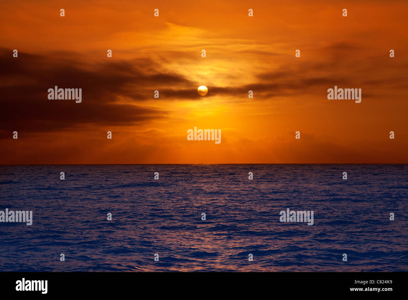 golden sunrise with sun and clouds over blue Mediterranean sea - Stock Image