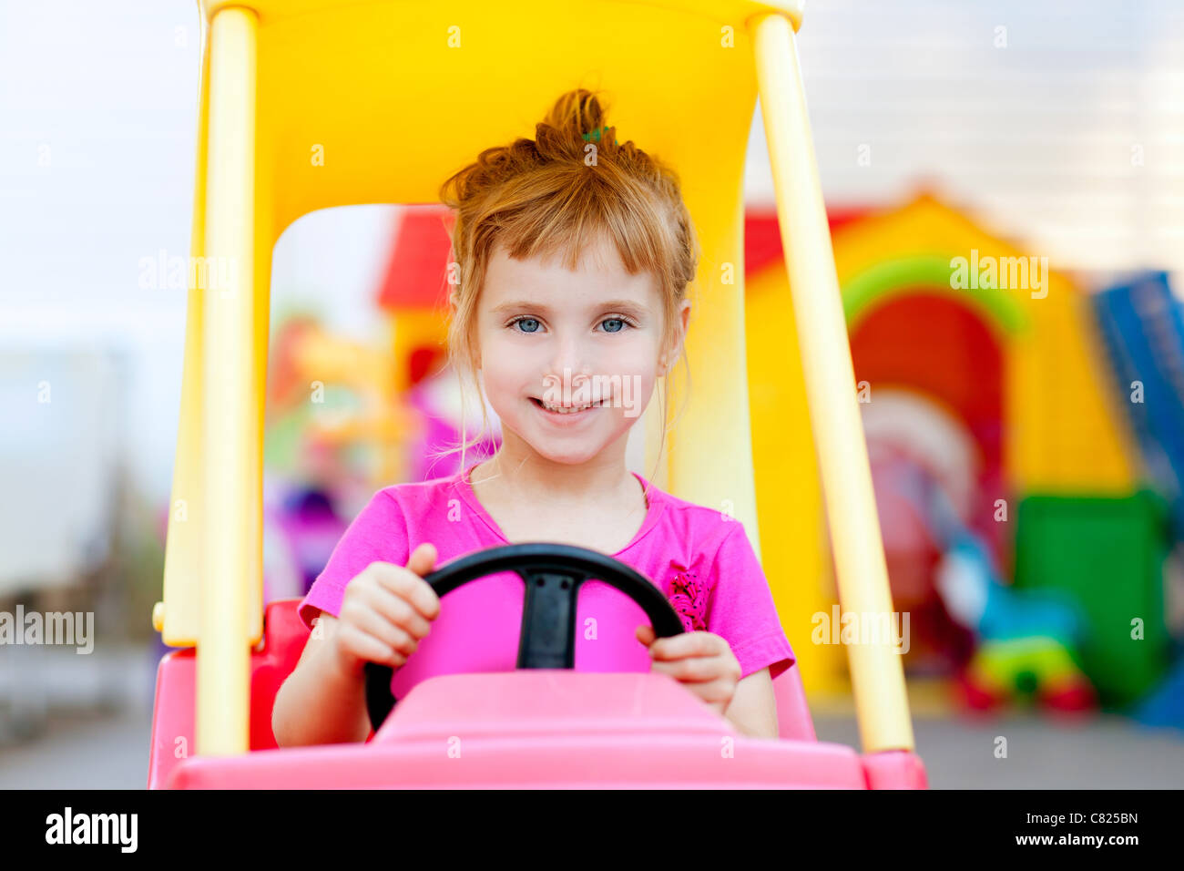 blond children girl driving toy car yellow Stock Photo