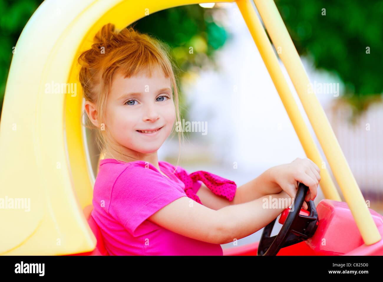 blond children girl driving toy car yellow Stock Photo
