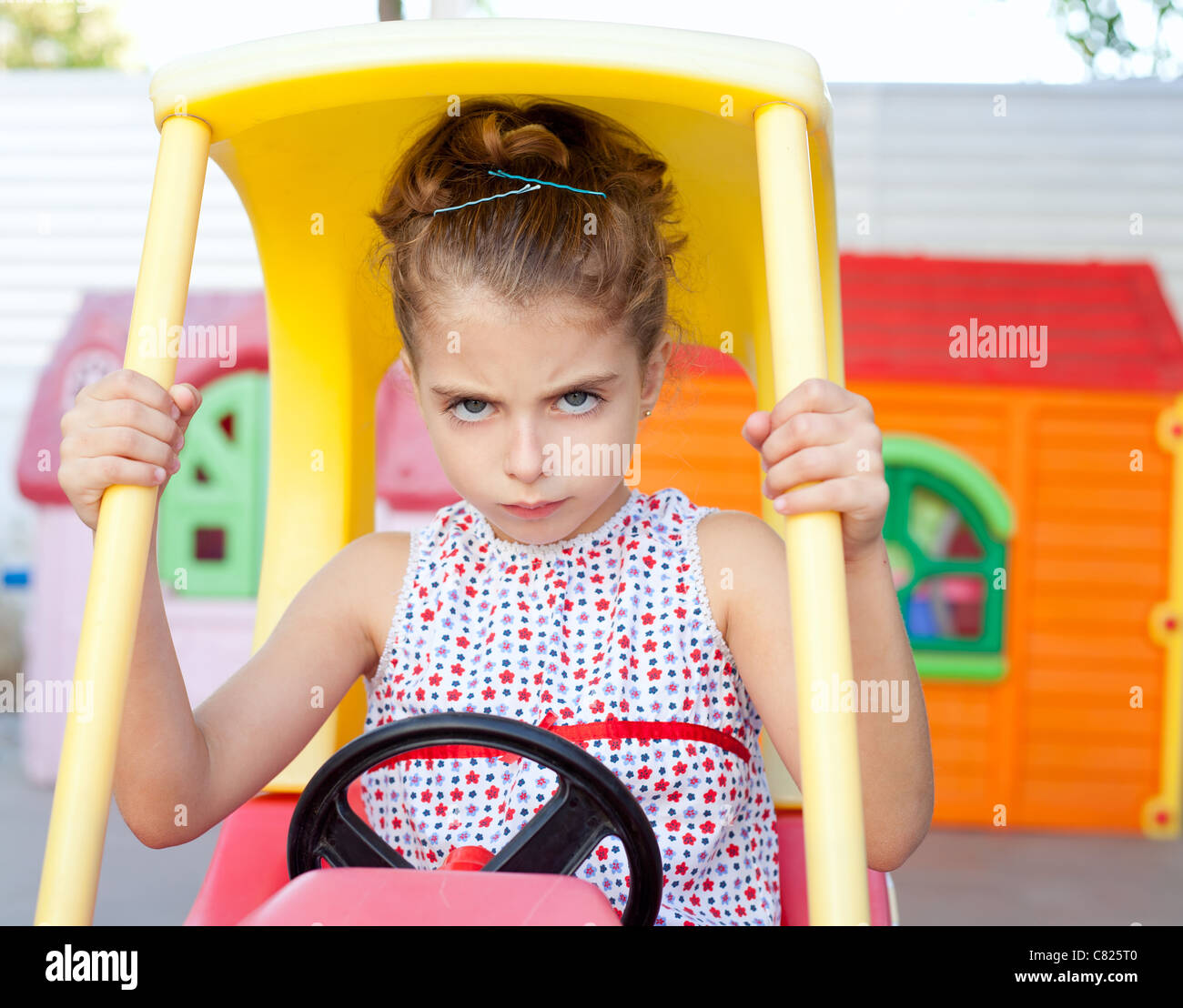 Angry toy car driver children girl in playground - Stock Image