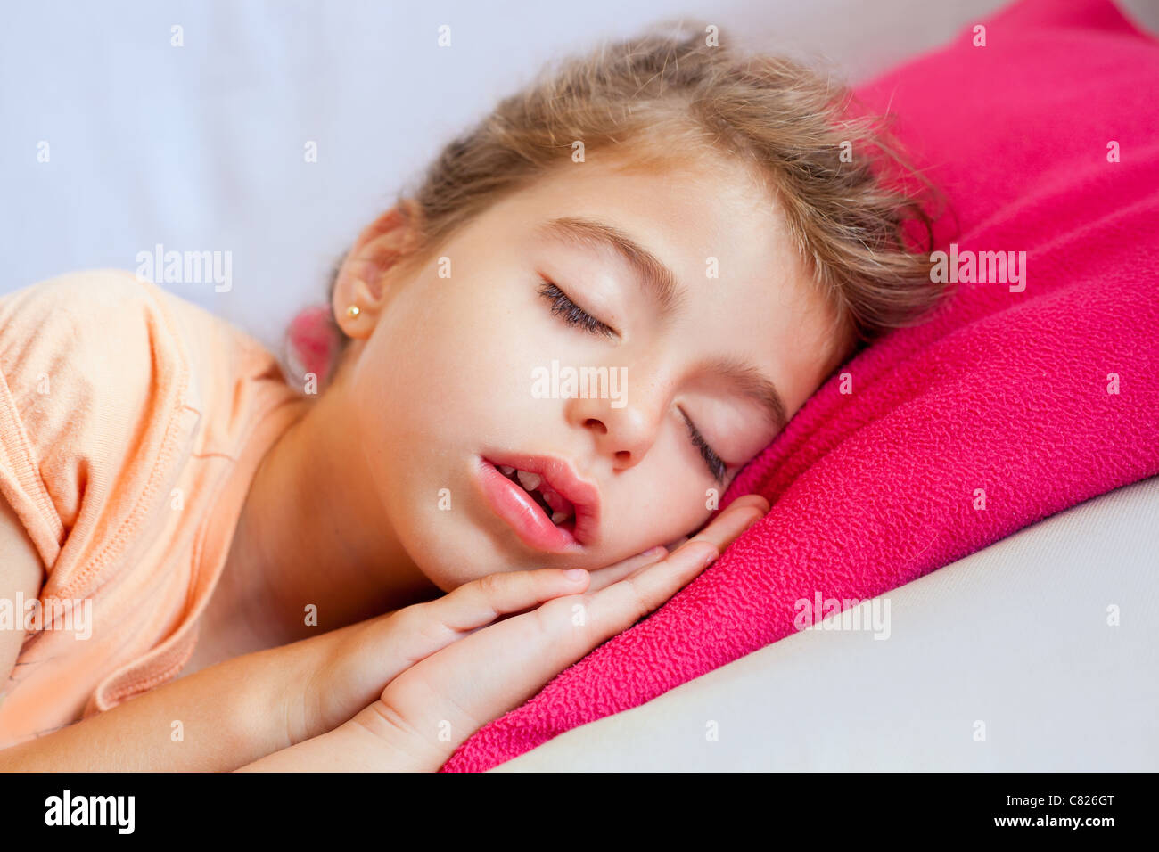 Deep sleeping children girl closeup portrait on pink pillow - Stock Image