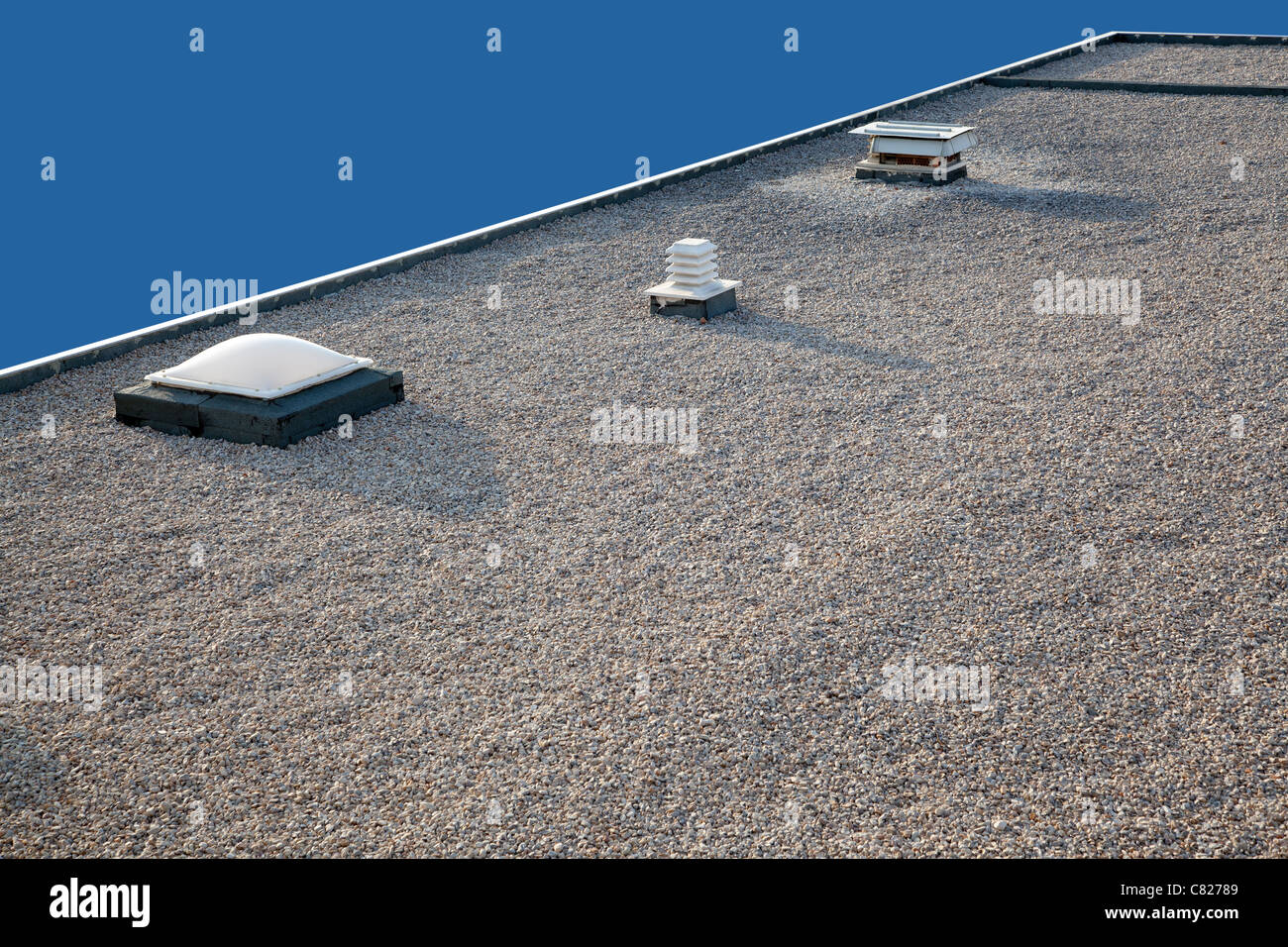 Inverted roof with chimney and skylight and gravel top - Stock Image