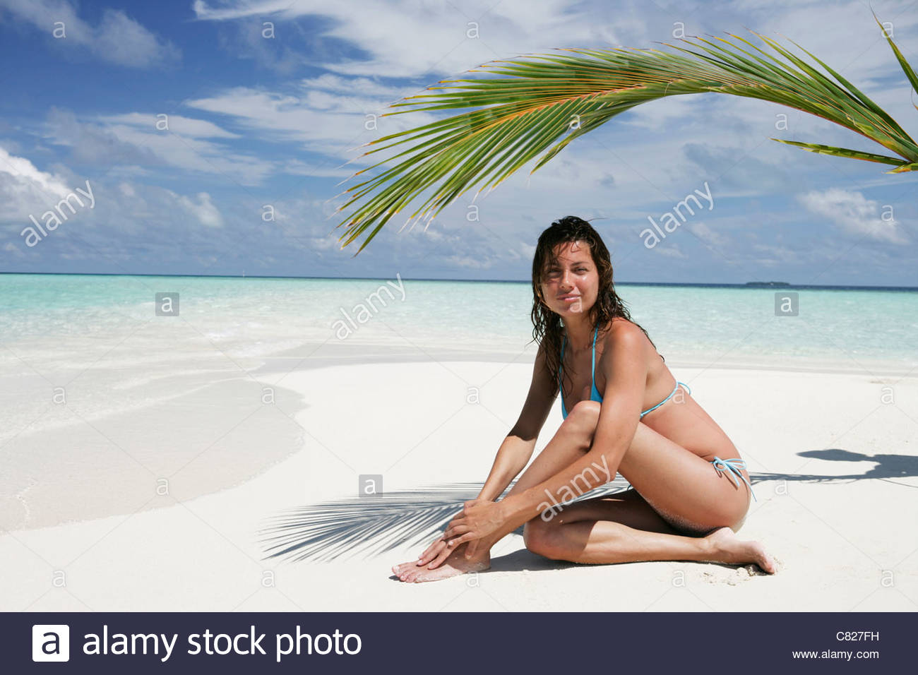 Woman's portrait sitting on beach - Stock Image