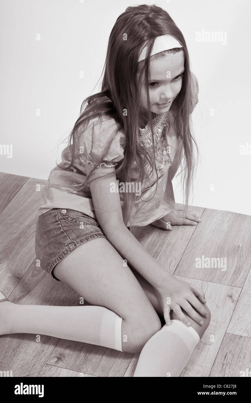 an eight-year-old girl sitting on the floor and looking shy - Stock Image