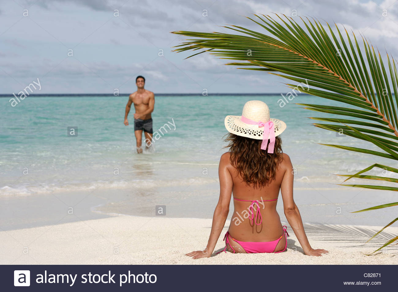 Woman sitting on the beach and man coming out of the water - Stock Image