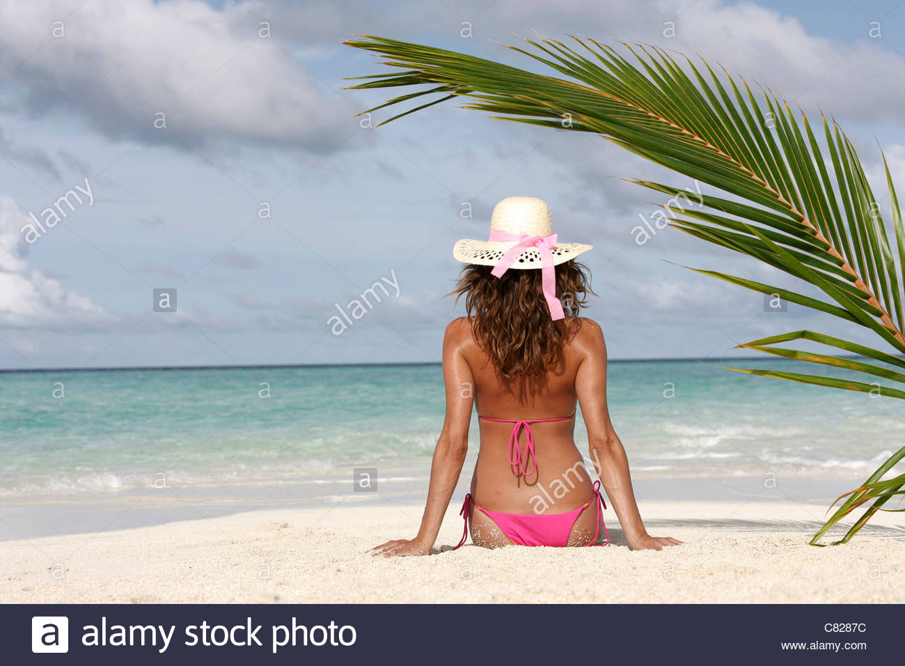 Woman sitting on the beach - Stock Image