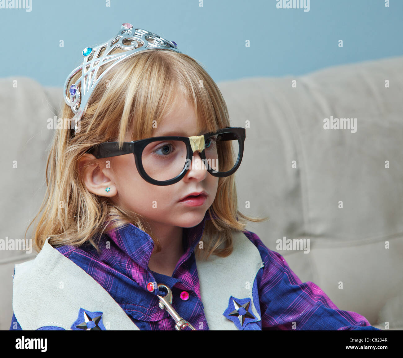 Little girl with black nerd glasses and tiara. - Stock Image