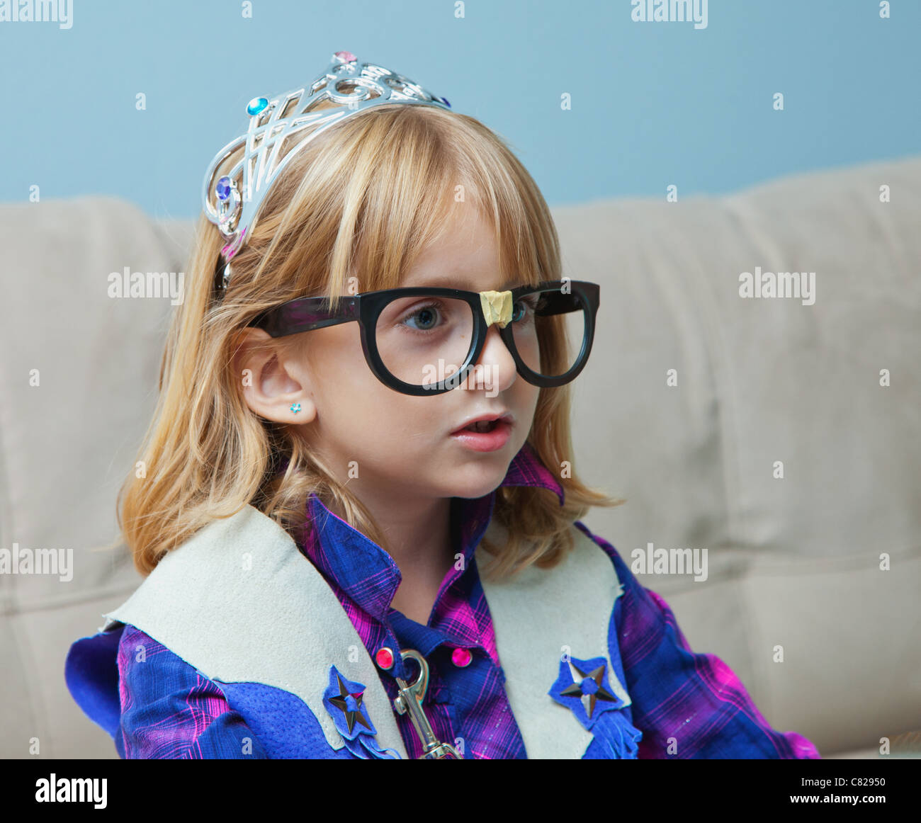Little girl with nerd black glasses and tiara. - Stock Image