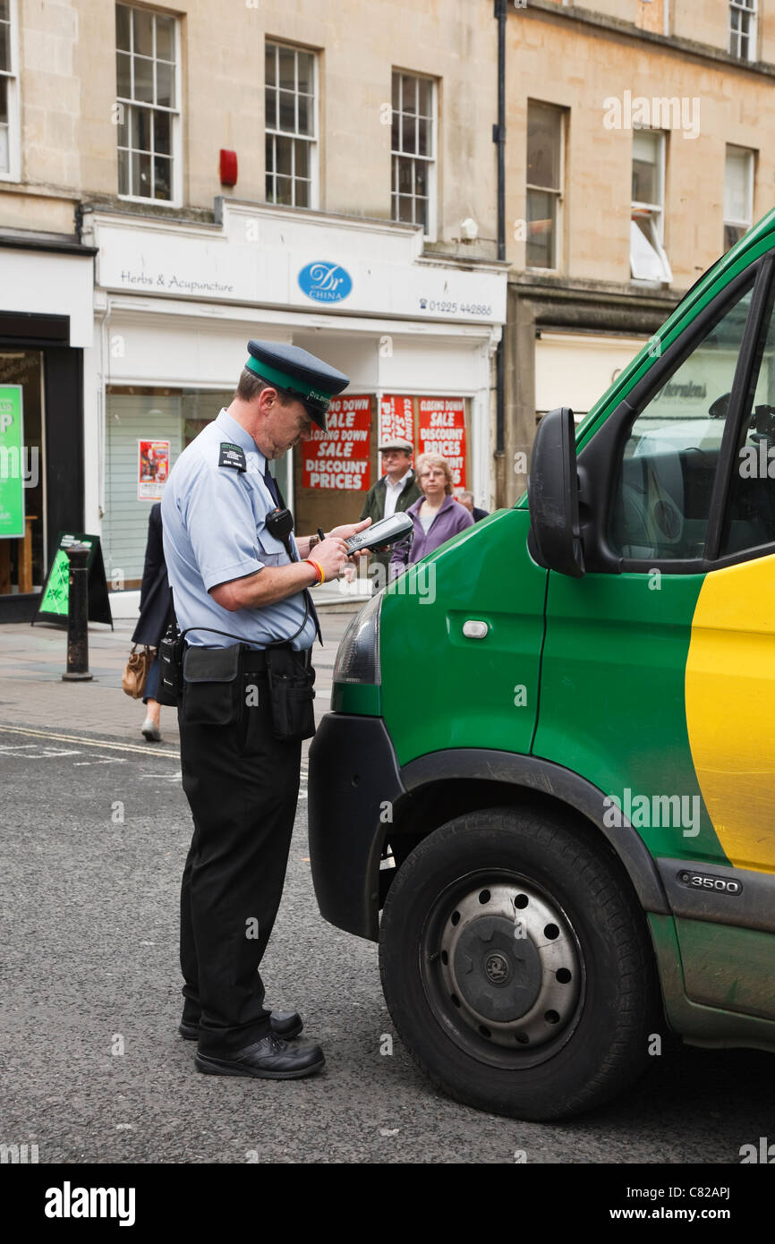 Traffic Warden or Civil Enforcement Officer issuing a parking offence ticket to a delivery van illegally parked - Stock Image