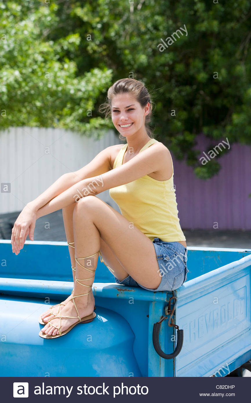 Woman sitting on a car - Stock Image