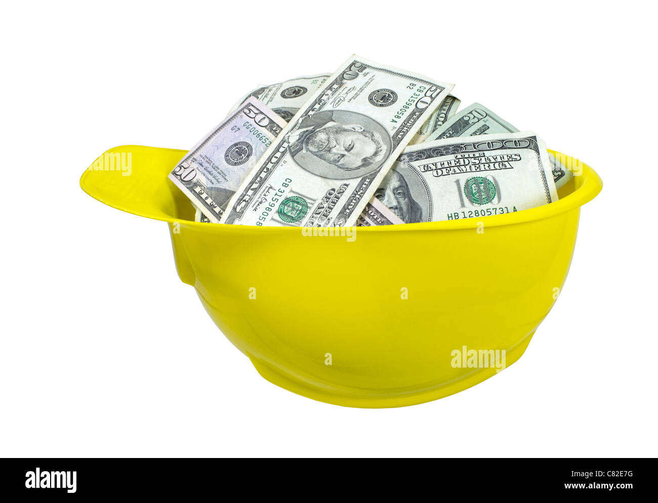 Yellow hard hat worn for protection when working on construction sites full of large amounts of money - path included - Stock Image