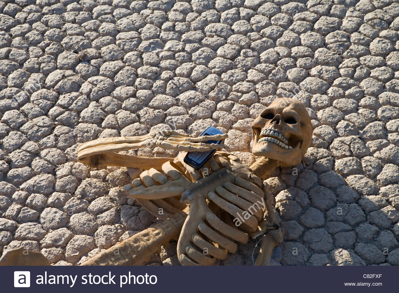 USA, California, Death Valley, skeleton and mobile on cracked earth - Stock Image