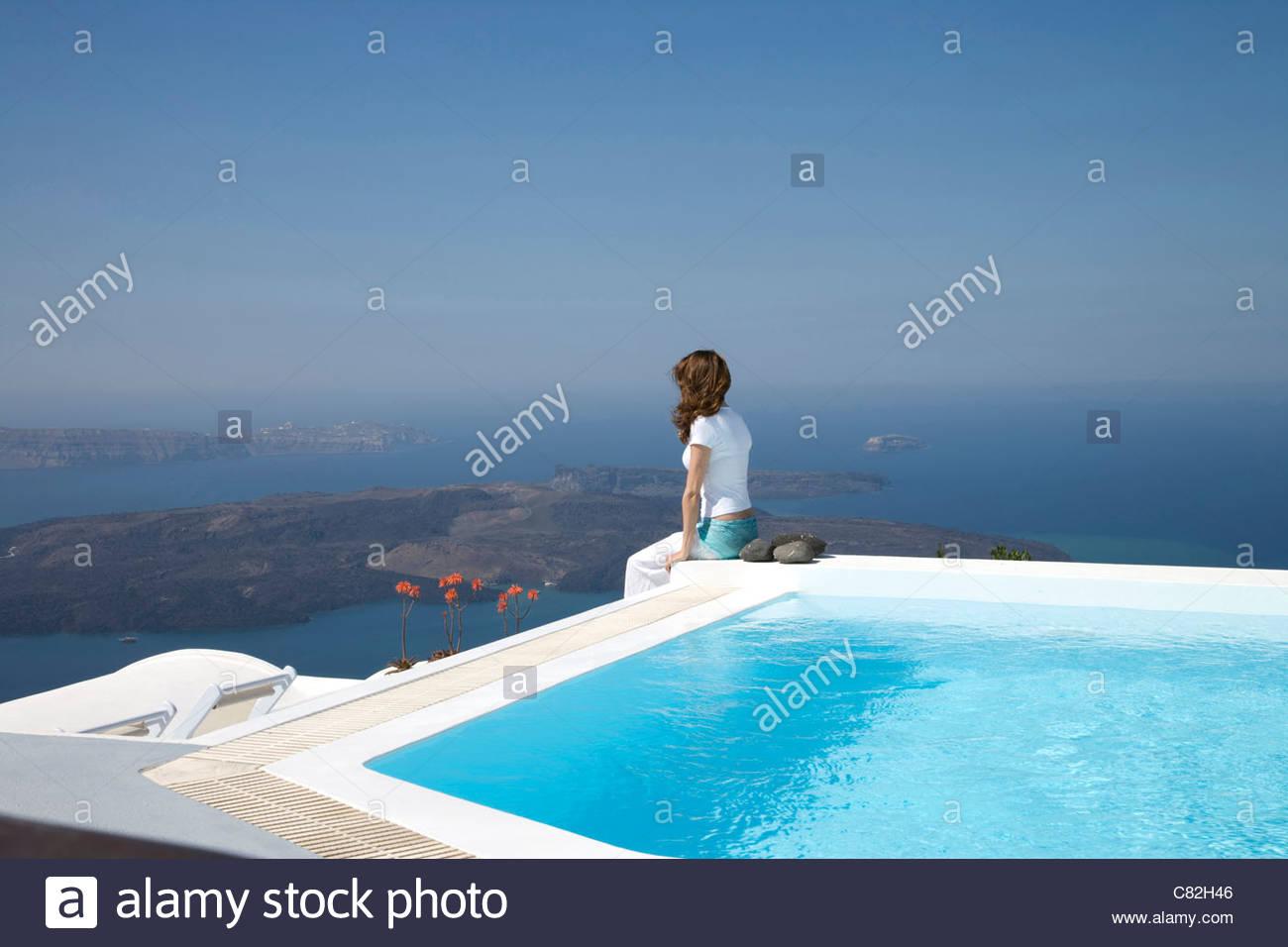 Greece, Santorini, Fira, young woman sitting by the pool - Stock Image