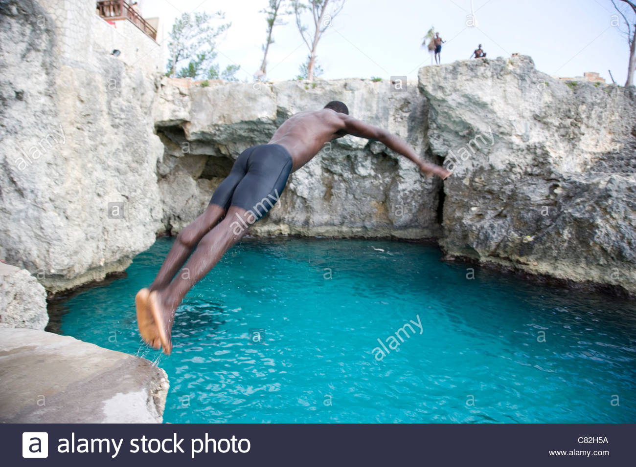 Caribbean, Jamaica, Negril,rear view of man diving into sea - Stock Image