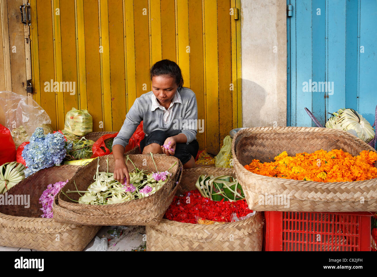 Balinese Woman making offerings to sell at the Ubud Traditional Markets. Ubud, Bali, Indonesia - Stock Image