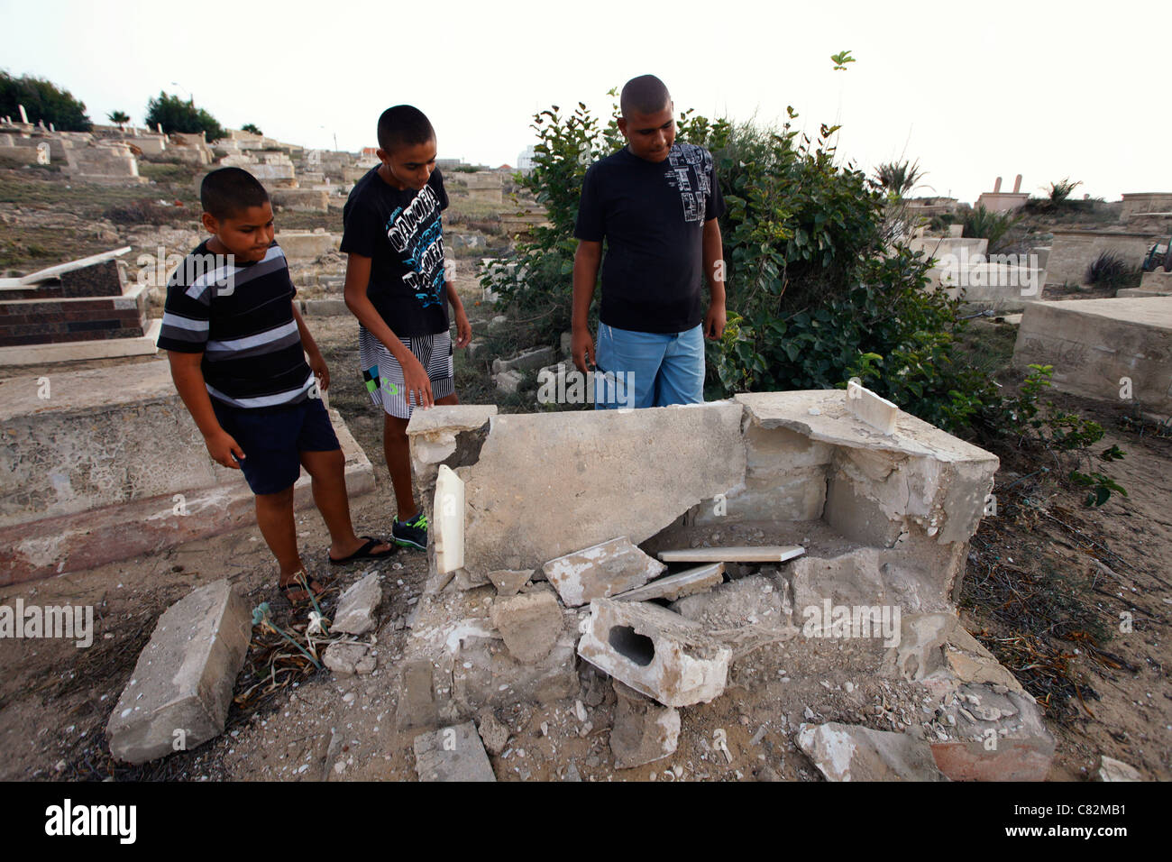 Young Israeli Arabs looking at a shattered tomb at the Muslim cemetery in Jaffa a mixed Jewish Arab neighbourhood - Stock Image