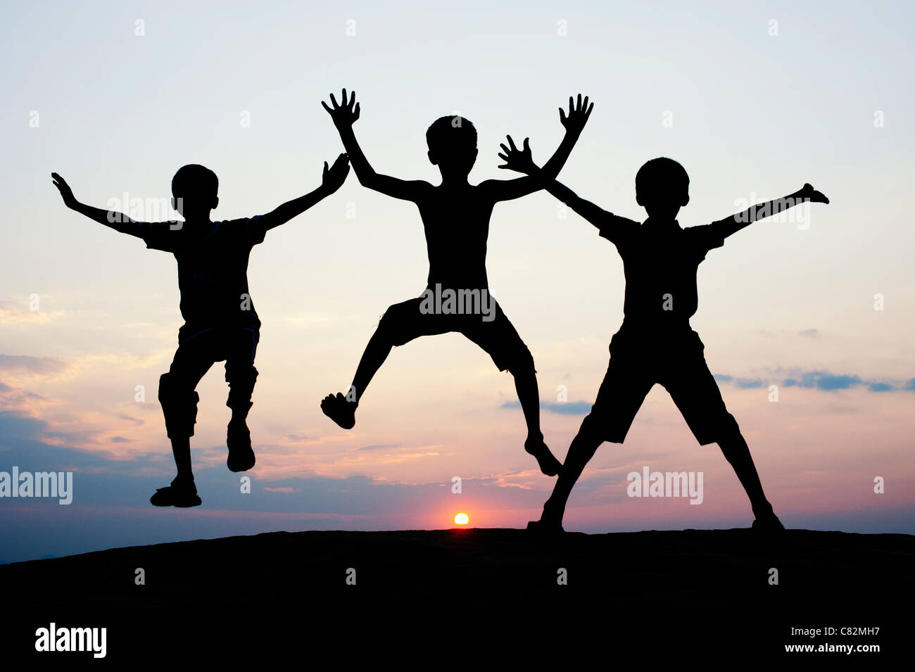 Silhouette of young Indian boys jumping against at sunset. India - Stock Image