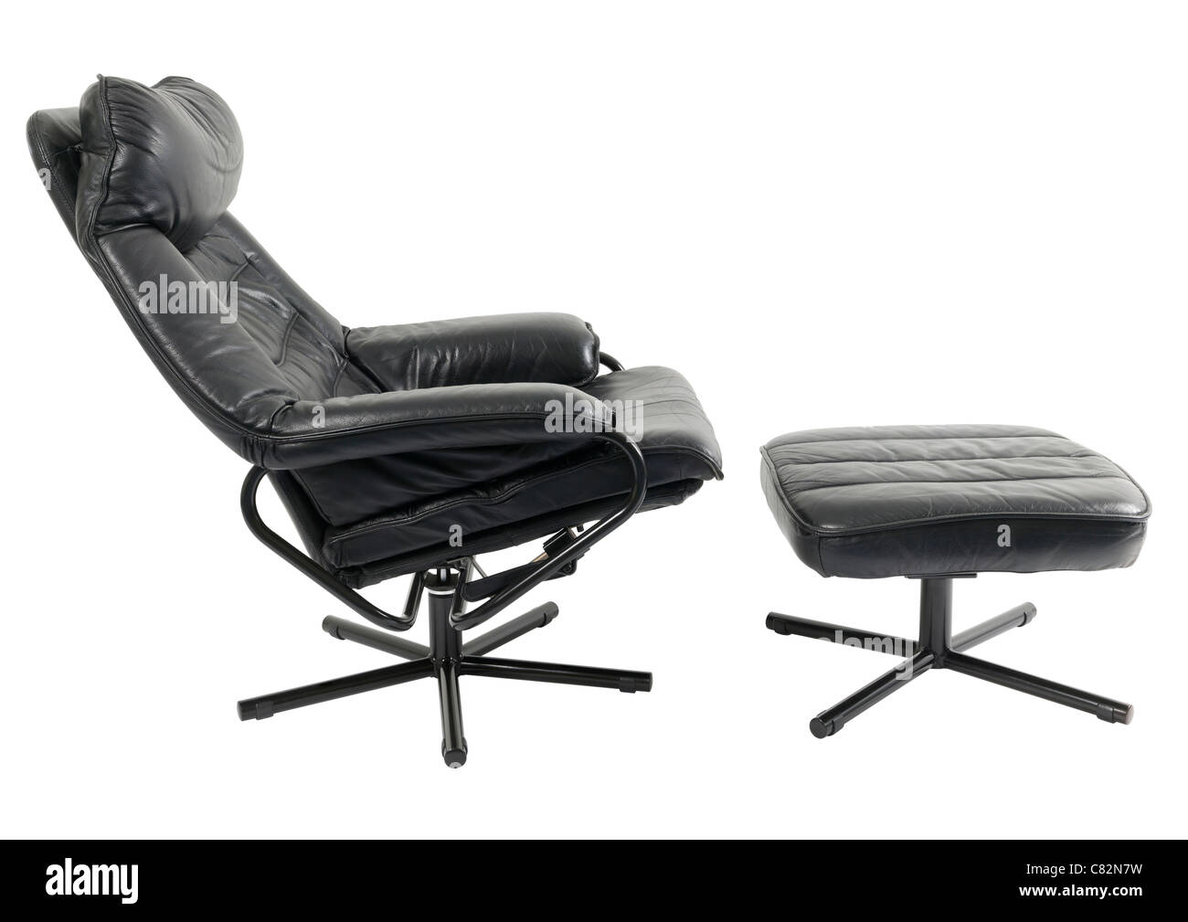 Black leather reclining chair and footstool on white background - Stock Image