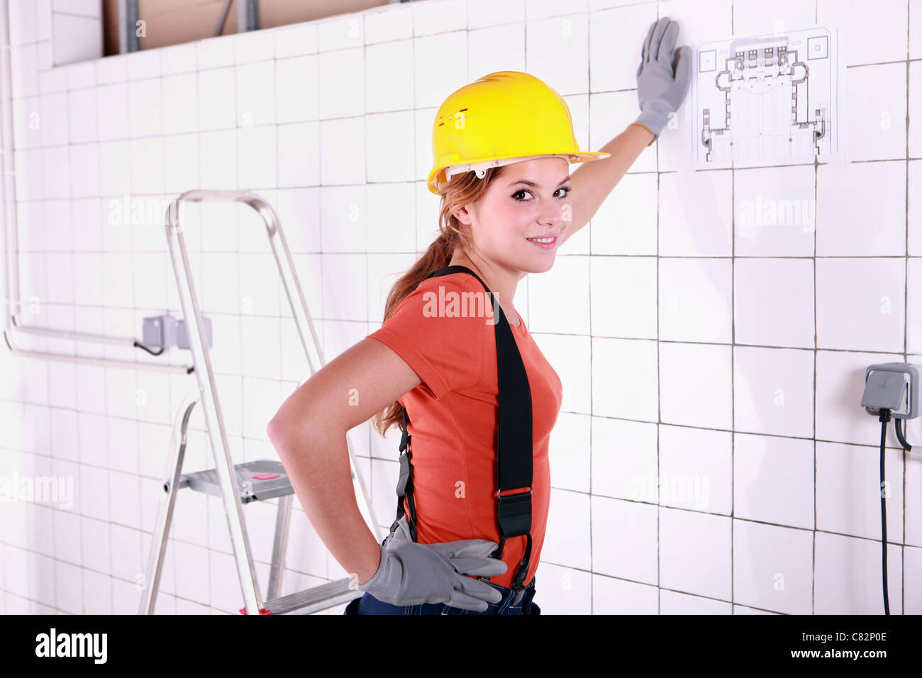 Young woman laborer leaning on a wall Stock Photo