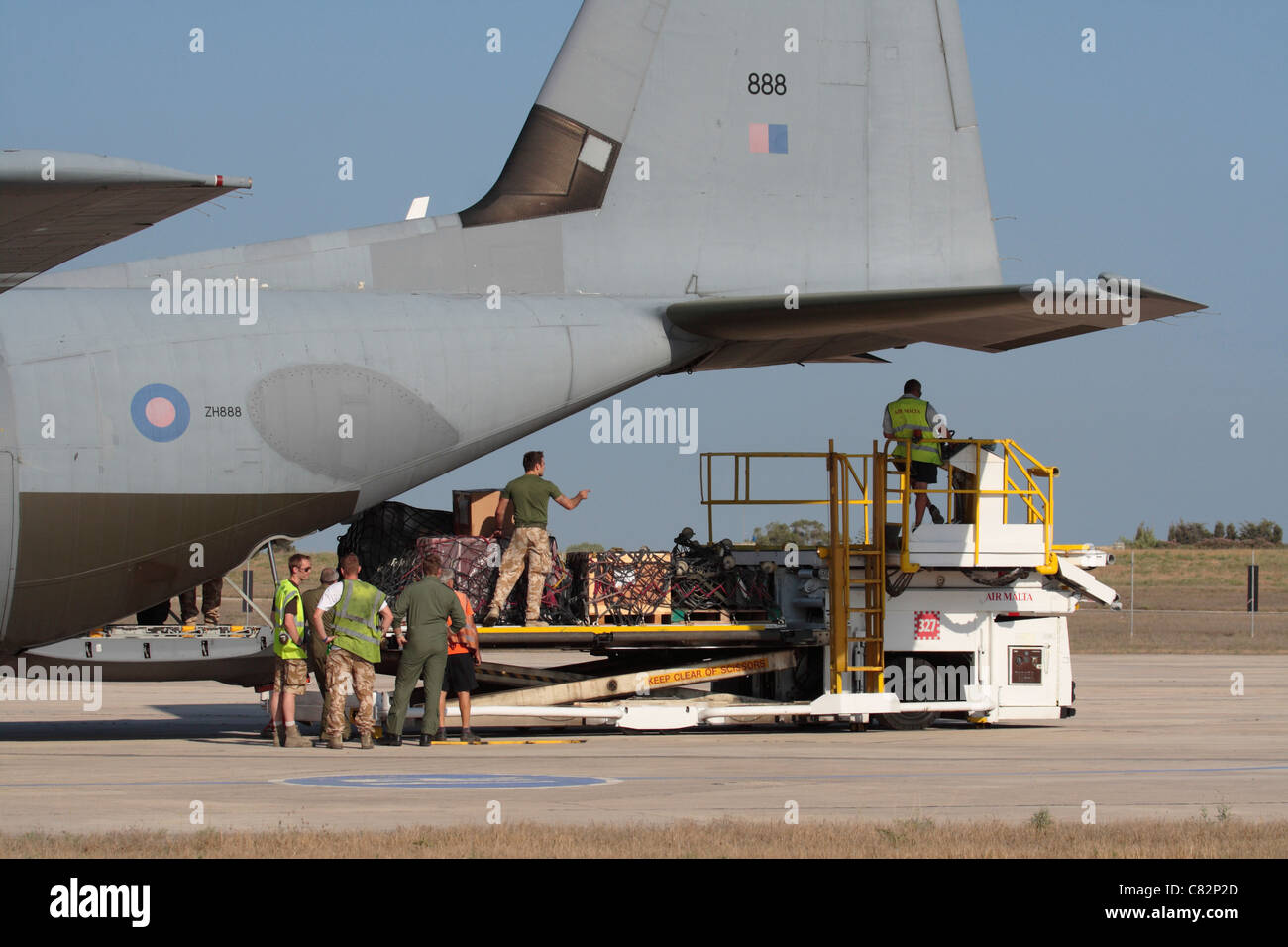 Military logistics. Unloading supplies from a Royal Air Force Hercules C5 transport plane - Stock Image