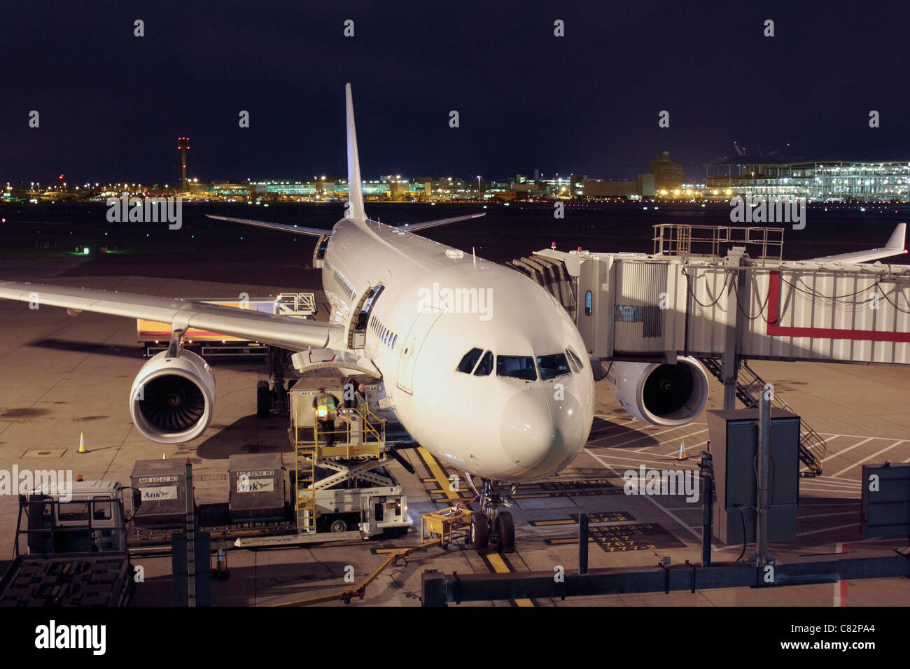Unmarked Airbus A330-200 airliner at its gate at Heathrow Airport Terminal 4, with air cargo being loaded on board. - Stock Image