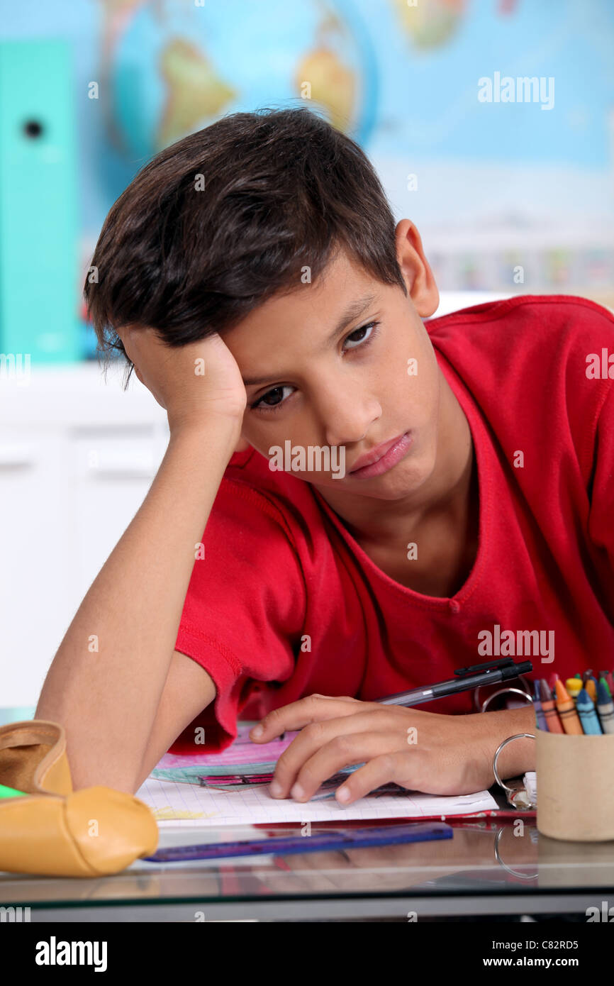 Bored little boy in classroom - Stock Image