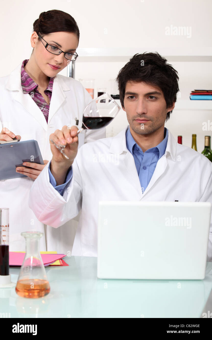 Man and woman testing wine in laboratory - Stock Image
