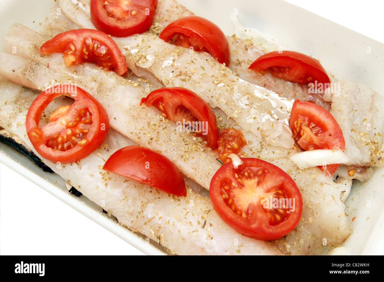 pollock / pollack fish fillets in dish for cooking sliced tomatoes & herbs (an alternative to cod) - Stock Image
