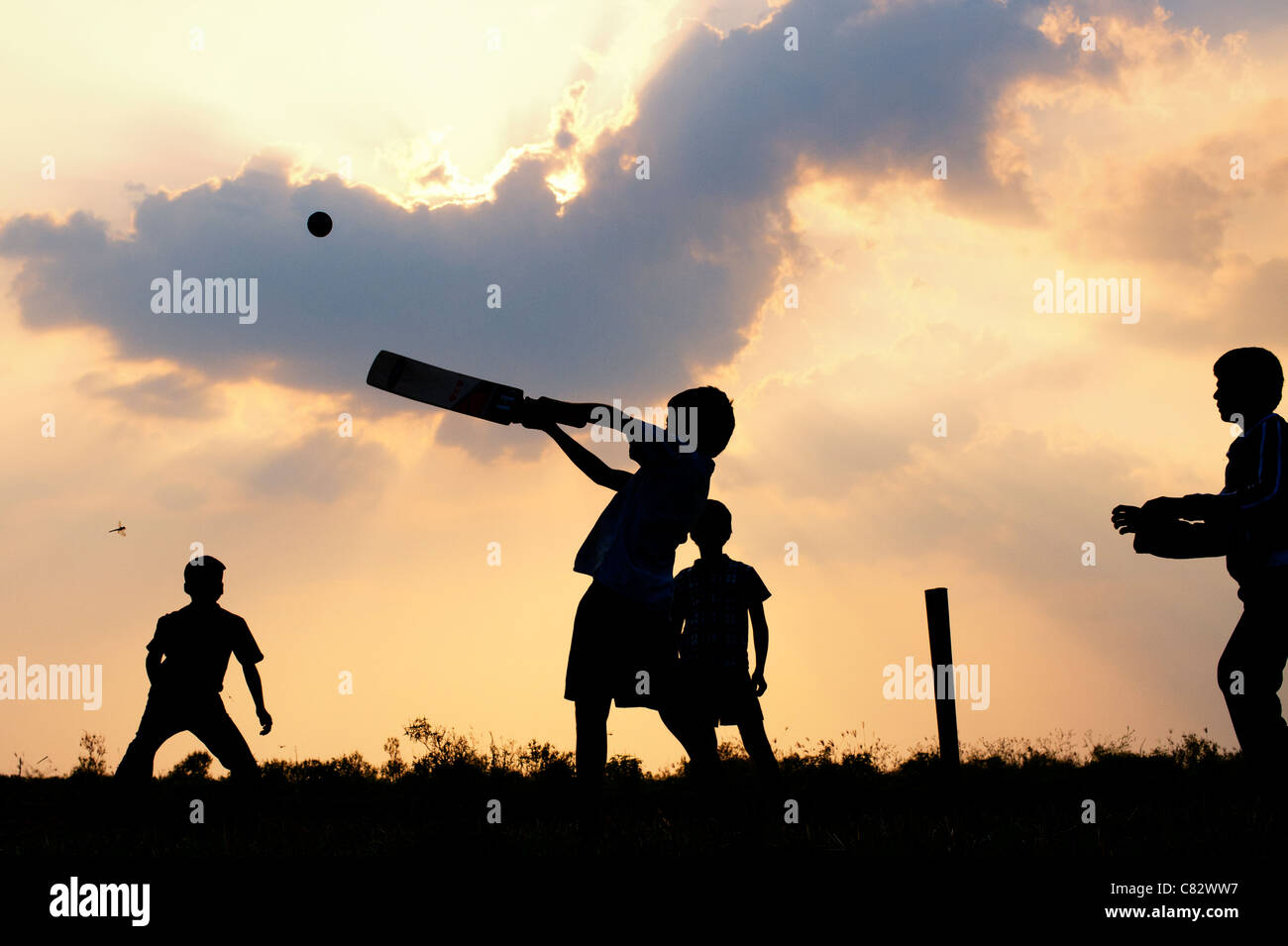Silhouette of young Indian boys playing cricket against a cloudy sunset background. India - Stock Image
