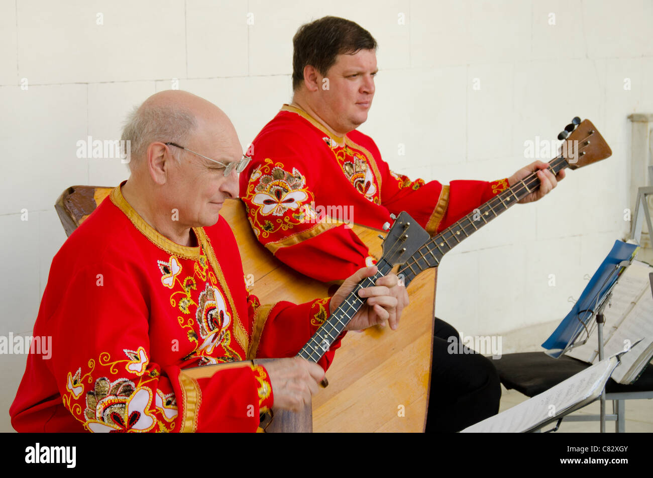 Ukraine, Yalta, Livadia Palace. Ukrainian folkloric show with traditional costumes. Men playing Russian three-stringed - Stock Image