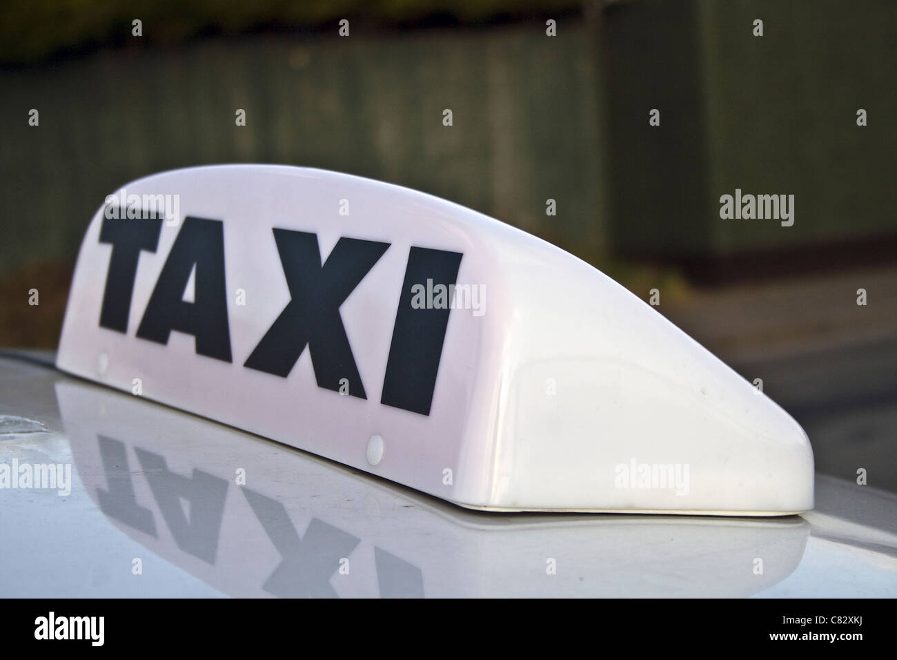 Close up of white taxi for hire sign and light from a hackney cab waiting for a fare on a taxi rank - Stock Image